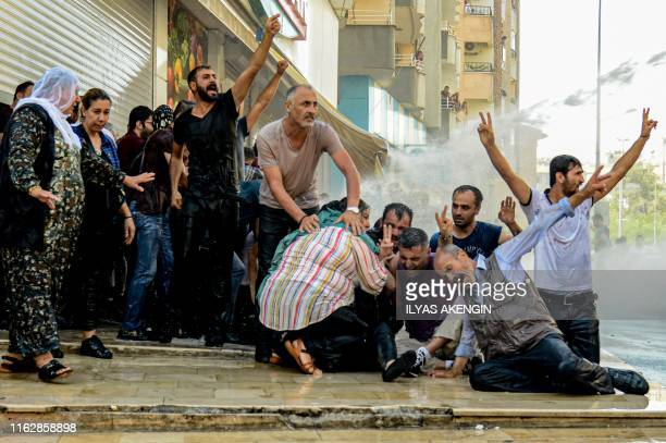Demonstrators are hit by water cannon as they protest against the replacement of Kurdish mayors with state officials in three cities, in Diyarbakir,...