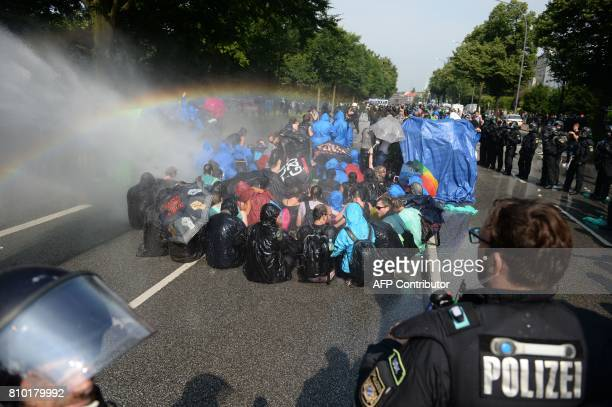 Demonstrators are hit by water cannons of the police as they protest on July 7 2017 in Hamburg northern Germany where leaders of the world's top...