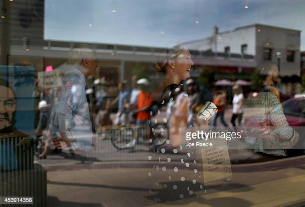 Demonstrators are reflected in the window of a restaurant as they walk through the street near the Buzz Westfall Justice Center where a grand jury...