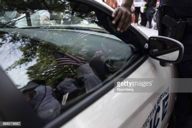 Demonstrators are reflected on a police vehicle as an officer stands guard outside of the Robert F Kennedy Department of Justice building during a...