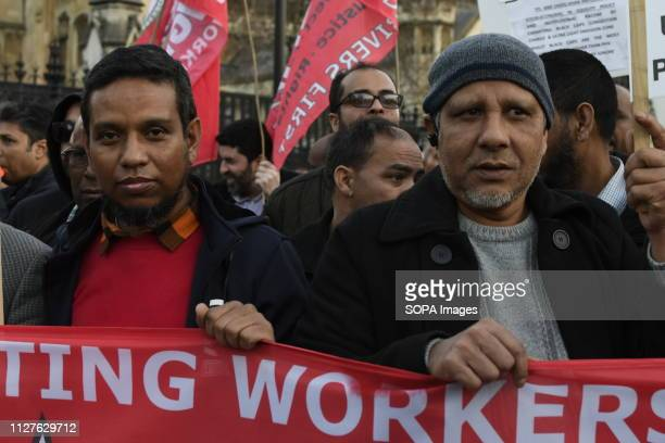 Demonstrators are seen behind a banner during the protest Minicab drivers blocked Parliament Square in protest over changes to the congestion charge...