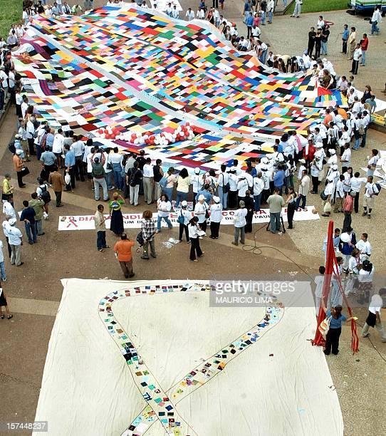 Demonstrators are seen during Worlds AIDS day in Sao Paulo Brazil 30 November 2001 Centenares de portadores del virus HIV sostienen una tela colorida...