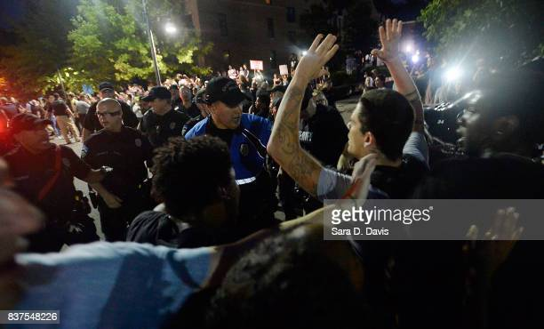 Demonstrators are shoved by police during a rally for the removal of a Confederate statue coined Silent Sam on the campus of the University of Chapel...