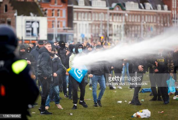 Demonstrators are sprayed by police water cannon at Amsterdam's Museumplein during a protest against the lockdown imposed to curb the spread of the...