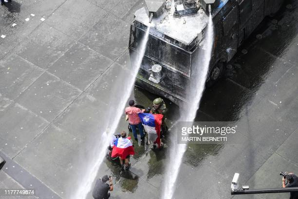 Demonstrators are sprayed with water by riot police in Santiago on the sixth straight day of street violence which erupted over a now suspended hike...