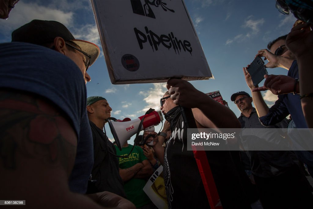 Demonstrators argue with a counter demonstrator holding a sign during an 'America First' demonstration on August 20, 2017 in Laguna Beach, California. Organizers of the rally describe it as a vigil for victims of illegal immigrants and refugees. Opponents say the demonstration is steeped in racism.