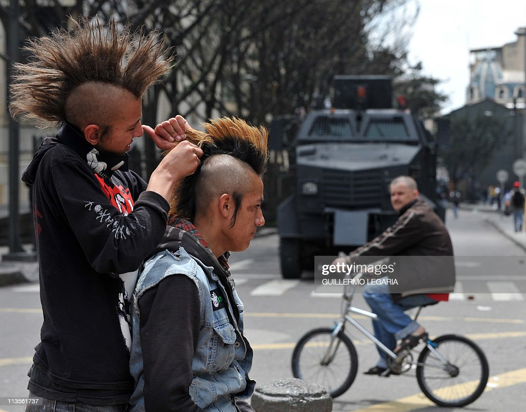 Demonstrators arrange their hair in front of an anti-riot water cannon during a May Day demonstration in Bogota, Colombia, on May 1, 2011. AFP PHOTO/Guillermo LEGARIA