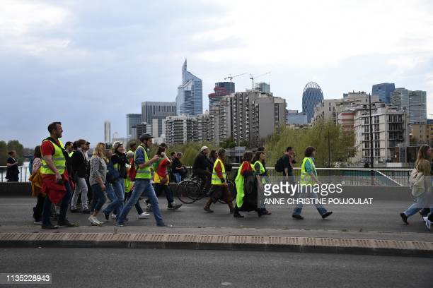 Demonstrators arrive in Courbevoie with La Defense district in background during yellow vest protests in Paris on April 6 as demonstrations are...