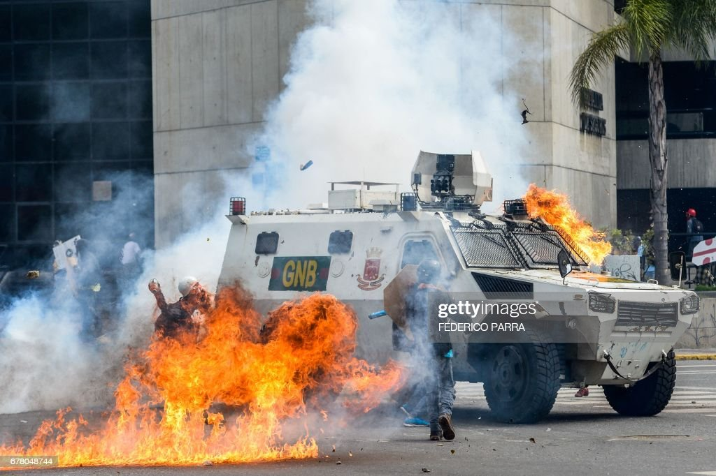 TOPSHOT - Demonstrators assault and set on fire a National Guard riot control vehicle during a protest against Venezuelan President Nicolas Maduro, in Caracas on May 3, 2017. Venezuela's angry opposition rallied Wednesday vowing huge street protests against President Nicolas Maduro's plan to rewrite the constitution and accusing him of dodging elections to cling to power despite deadly unrest. /