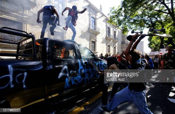 Demonstrators attack a police vehicle during a protest following the death of a young man while in police custody, after he had been arrested...