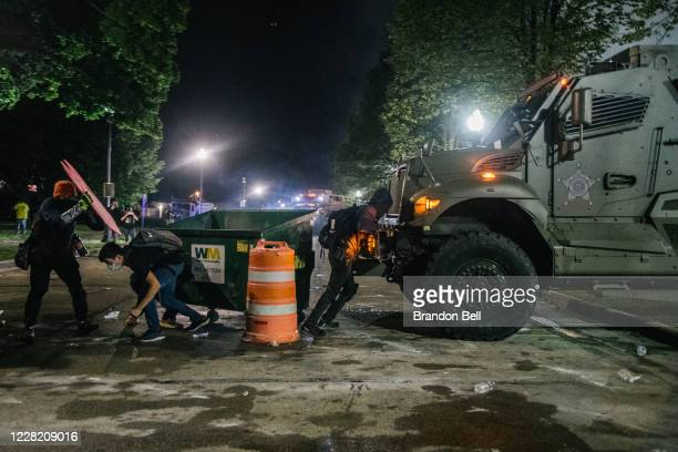 Demonstrators attempt to block an armored police vehicle on August 25 2020 in Kenosha Wisconsin As the city declared a state of emergency curfew a...