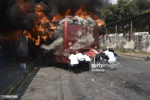 Demonstrators attempt to pull a bus that is on fire away from homes during clashes along the border in Urena Tachria state Venezuela on Saturday Feb...