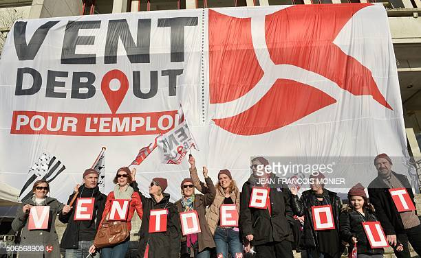 Demonstrators bear letters reading 'headwind' under a banner reading 'headwind for employment' on January 24 in front of the townhall of Brest...