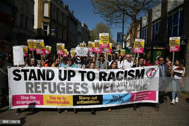 Demonstrators behind a giant banner chant with placards as they march during an antiracism protest called by the 'Stand Up To Racism' group in...