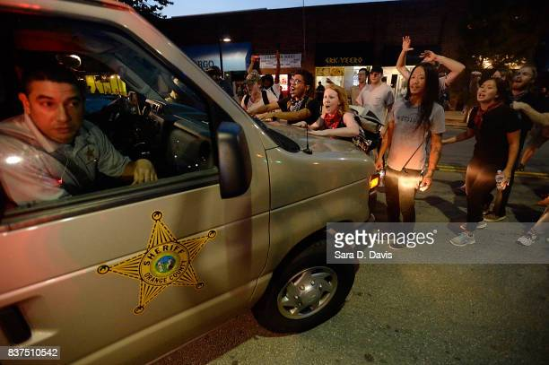 Demonstrators block a sheriff van from leaving with a man who was allegedly arrested for covering his face during a rally for the removal of a...