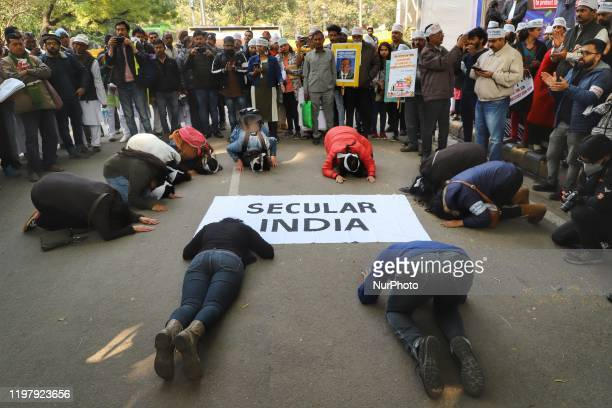 Demonstrators bow their head infront of a banner which reads 'Secular India' during a protest against the Citizenship Amendment Act and NRC at Jantar...