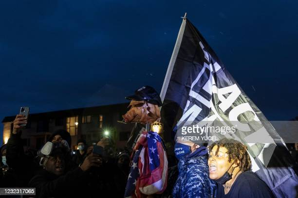 Demonstrators brandish a pig's head on a pike and fly a Black Lives Matter flag outside the Brooklyn Center police station while protesting the death...