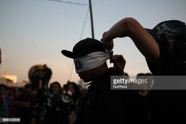 Demonstrators break a piñata with their eyes covered with a band written in Spanish with the word Indifference while marching to protest against the...