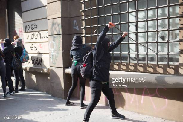Demonstrators break a window during a rally on International Women's Day in Mexico City Mexico on Friday March 8 2020 The United Nations first...