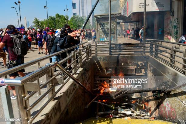 Demonstrators bring down a lamp post in Santiago on October 24, 2019 after a week of street violence which erupted against a now suspended metro fare...