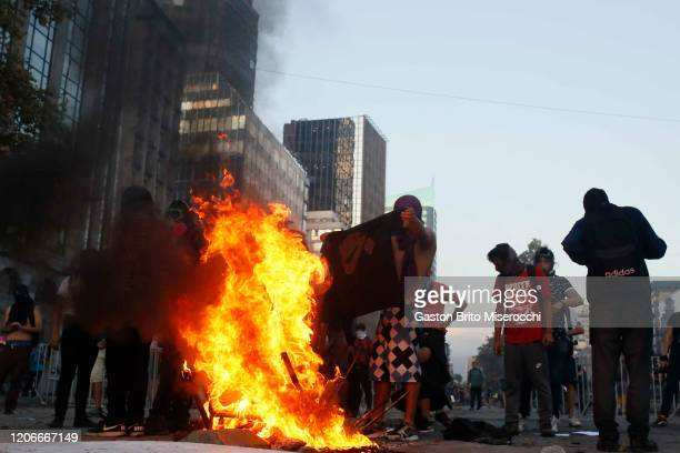 Demonstrators burn a barricade during protests against the government of Sebastián Piñera on its second anniversary on March 11 2020 in Santiago...