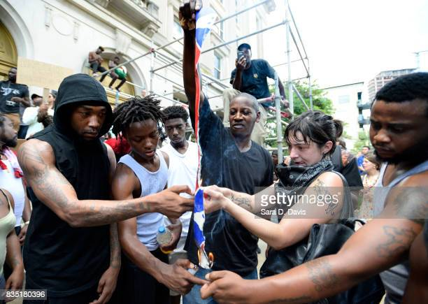 Demonstrators burn a Confederate flag replica in reaction to a potential white supremacists rally on August 18 2017 in Durham North Carolina The...