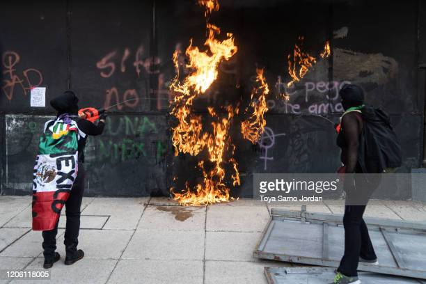 Demonstrators burn a wall during a rally on International Women's Day on March 8 2020 in Mexico City Mexico