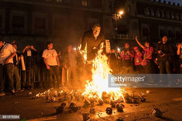 Demonstrators burn an effigy of US Presidentelect Donald Trump during a protest against the gasoline price hike in Mexico City Mexico on Monday Jan 9...
