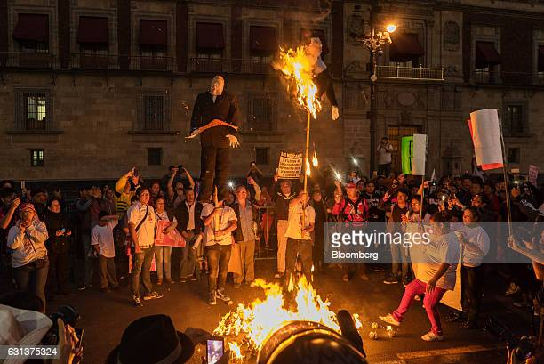 Demonstrators burn effigies of Mexico's President Enrique Pena Nieto right and US Presidentelect Donald Trump during a protest against the gasoline...