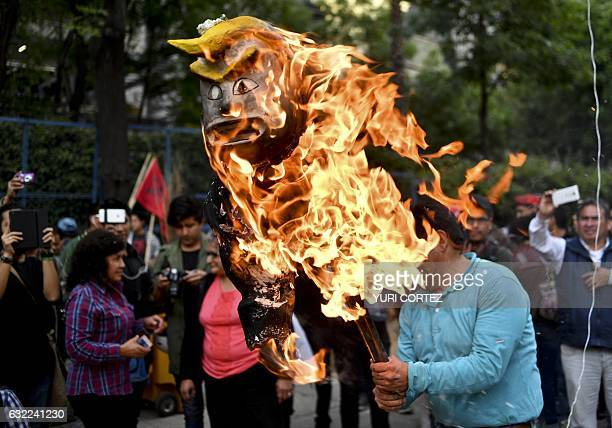 Demonstrators burn effigy representing US President Donald Trump in front of US Embassy compound in Mexico City on January 20 2017 Billionaire...