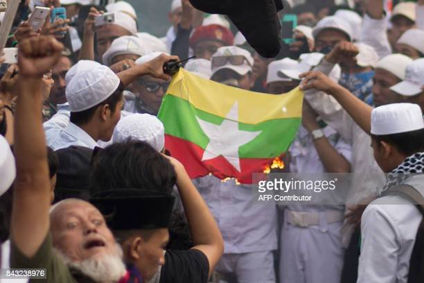 Demonstrators burn Myanmar's national flag during an antiMyanmar rally near its embassy in Jakarta on September 6 2017 Indonesian Muslims protested...
