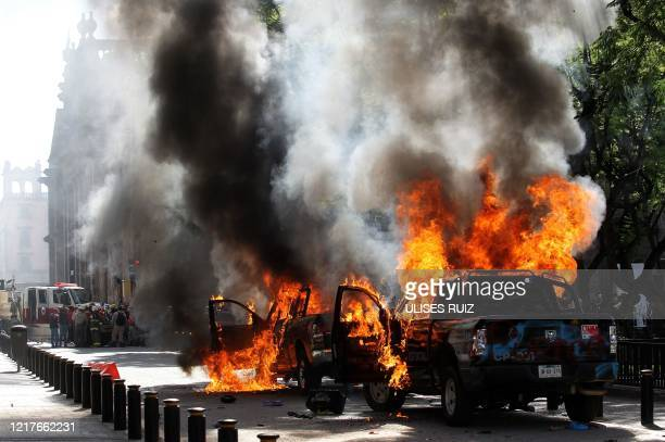 Demonstrators burn police vehicles during a protest following the death of a young man while in police custody after he had been arrested allegedly...