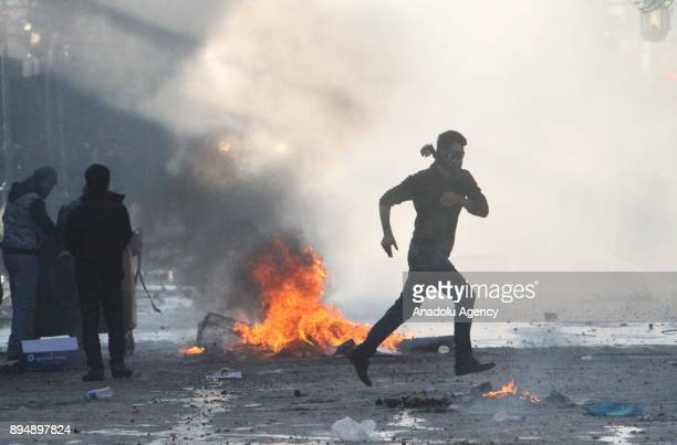 Demonstrators burn tires and block a road with a trash bin as they clash with riot police within antigovernment protests in Sulaymaniyah Iraq on...