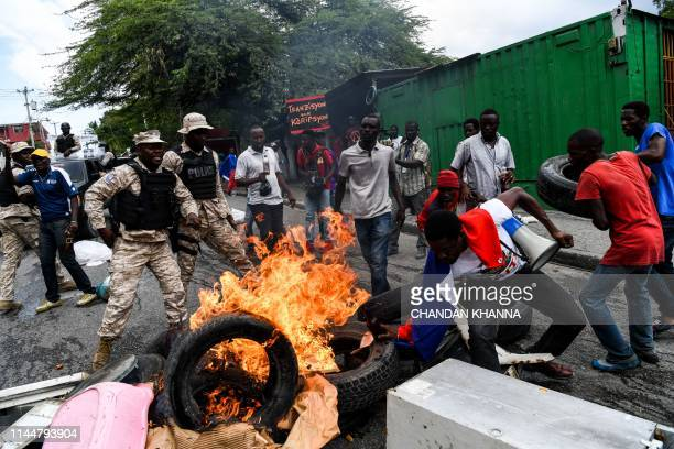 Demonstrators burn tyres during a protest against the ruling government on Haitian Flag Day in PortauPrince May 18 2019 Protesters marched through...