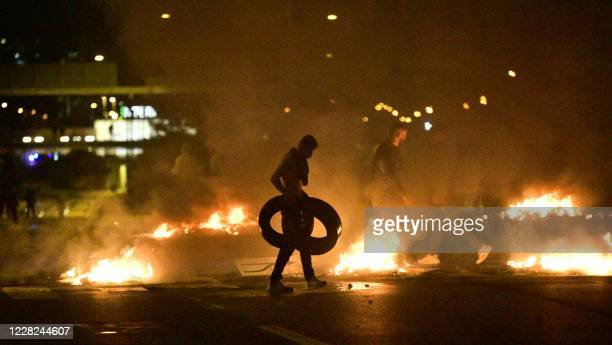 Demonstrators burn tyres during clashes with police in the Rosengard neighbourhood of Malmo Sweden on August 28 2020 The protest was sparked by the...