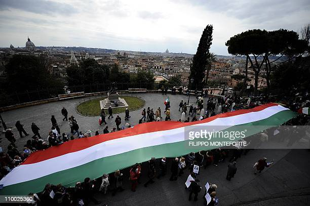 Demonstrators carry a 200meter long Italian flag during a demonstration to defend the Italian Constitution on March 12 2011 in downtown Rome AFP...