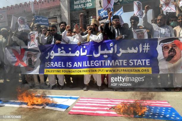 Demonstrators carry a banner showing crossed-out portraits of Israel's Prime Minister Benjamin Netanyahu , Abu Dhabi Crown Prince Sheikh Mohammed bin...
