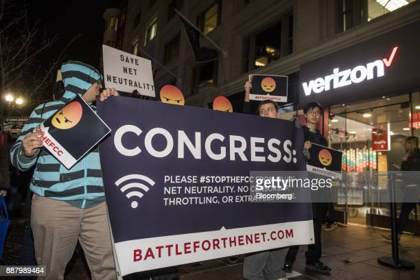 Demonstrators carry a banner while holding up angry emoji signs during a net neutrality protest outside a Verizon Communications Inc store in Boston...