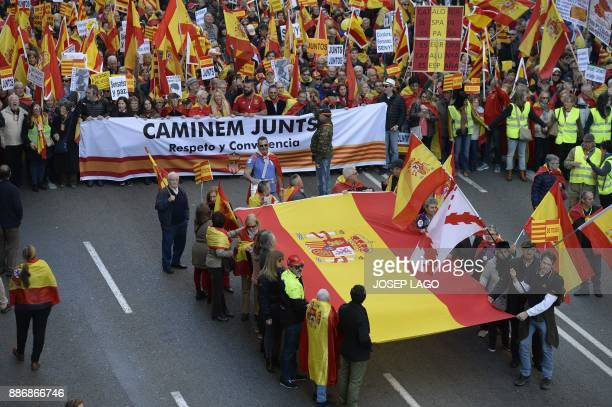 Demonstrators carry a big Spanish flag and march holding a banner reading 'Let's walk together Respect and coexistence' during an againstindependence...