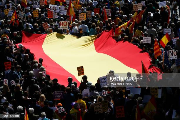 TOPSHOT Demonstrators carry a big Spanish flag during a demonstration called by 'Sociedat Civil Catalana' to support the unity of Spain in Barcelona...
