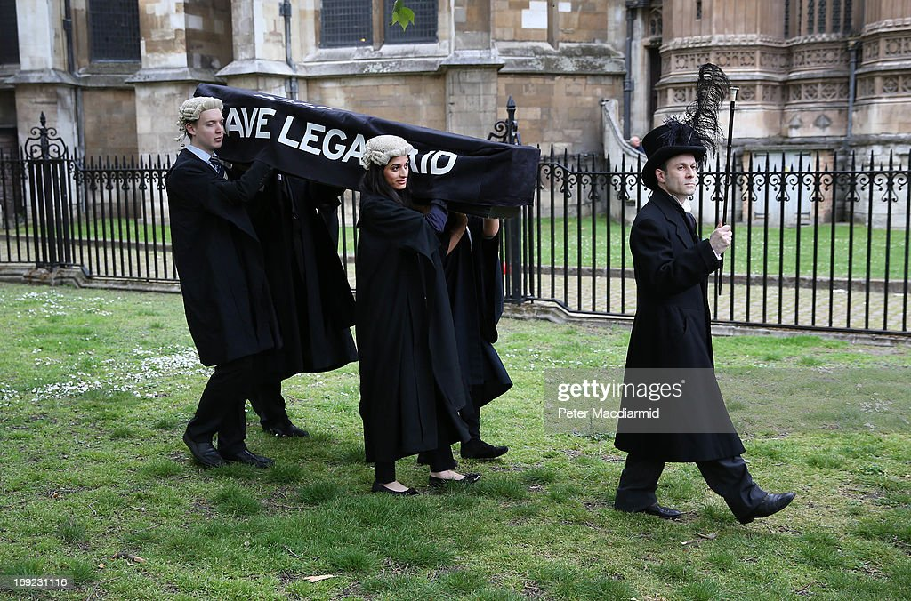 Demonstrators carry a coffin representing the death of Legal Aid near Parliament on May 22, 2013 in London, England. Lawyers are calling on the government to halt planned cuts to the system of legal aid in the United Kingdom.