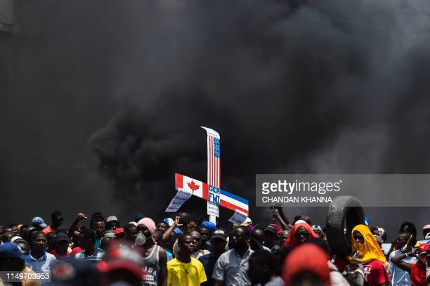 TOPSHOT Demonstrators carry a cross bearing images of Canada US and French flags during a protest march against the ruling government in PortauPrince...