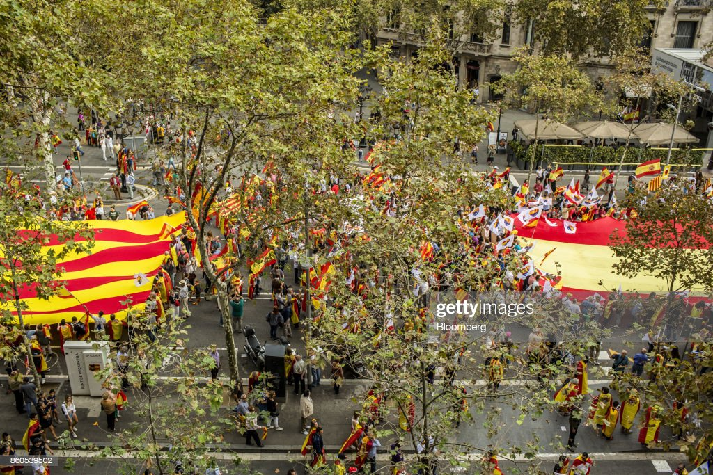 Demonstrators carry a large Catalan flag, also known as the Senyera, left, and a Spanish National flag in support of Spanish unity during a march on Spain's National Day in Barcelona, Spain, on Thursday, Oct. 12, 2017. Prime Minister Mariano Rajoy gave his Catalan antagonist Carles Puigdemont five days to clarify whether he has declared independence from Spain or not as the country prepared for its national holiday on Thursday. Photographer: Angel Garcia/Bloomberg via Getty Images