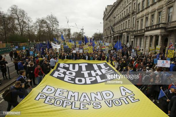 Demonstrators carry a large yellow banner reading 'Put It To The People Demand a People's Vote' as they march on Piccadilly during the antiBrexit...