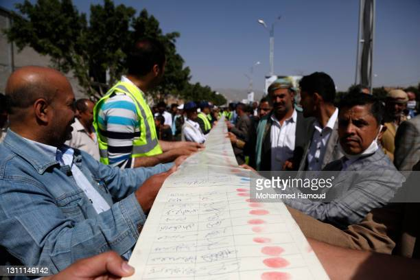 Demonstrators carry a long document with thousands of signatures condemning the Saudi-led coalition and also blaming the UN for the fuel crisis, as...