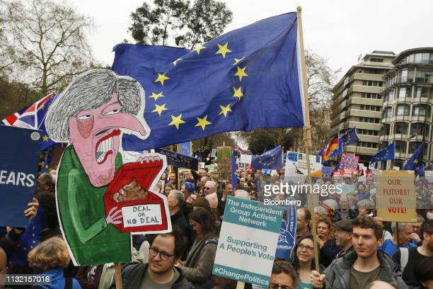 Demonstrators carry a placard depicting Theresa May UK prime minister and European Union flags as they march during the antiBrexit People's Vote...