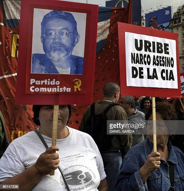 Demonstrators carry a portrait of the number two leader of the Marxist FARC rebels Raul Reyes and a poster against Colombian president Alvaro Uribe...