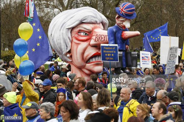 Demonstrators carry a sculpture in the likeness of of Theresa May UK prime minister as they stand on Park Lane during the antiBrexit People's Vote...