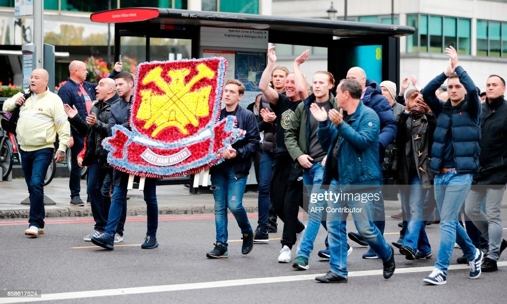 Demonstrators carry a West Ham United-themed wreath as they arrive to participate in a march by the Football Lads Alliance (FLA), from Pall Mall to Westminster Bridge, in London on October 7, 2017. The Football Lads Alliance (FLA), a self-described anti-extremist group of football fans, gathered on Pall Mall before planning to march to Westminster, to demonstrate concern at the 'recent upsurge' of terror attacks in the UK. / AFP PHOTO / Tolga AKMEN