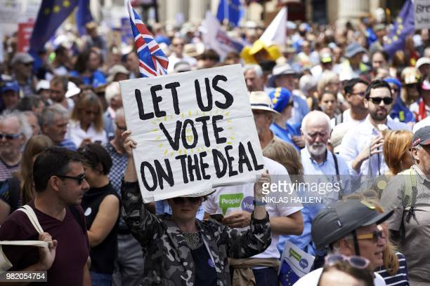 Demonstrators carry banners and flags as they participate in the People's March demanding a People's Vote on the final Brexit deal in central London...
